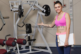 Smiling female trainer with clipboard pointing toward lat machine in gym