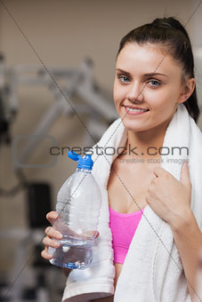 Portrait of a smiling woman with water bottle in gym