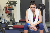 Tired and thoughtful woman in gym