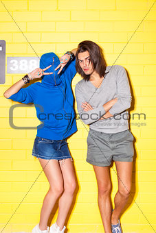 young people having fun in front of yellow brick wall