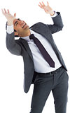 Scared businessman with arms raised