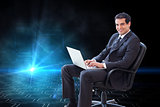 Composite image of businessman sitting on an armchair working with a laptop