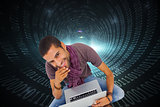 Composite image of man sitting on floor using laptop and smiling at camera