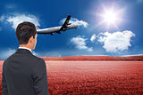 Composite image of businessman watching plane taking off