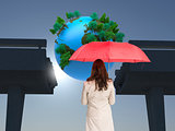 Composite image of businesswoman standing holding red umbrella