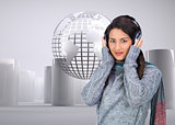 Composite image of model wearing winter clothes listening to music