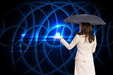 Composite image of businesswoman holding black umbrella