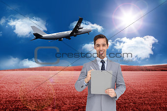 Composite image of businessman holding a clipboard