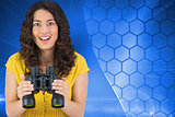 Composite image of smiling young woman holding binoculars