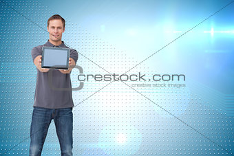 Composite image of young man showing his tablet computer
