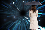Composite image of rear view of businesswoman holding umbrella