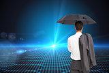 Composite image of businessman standing holding umbrella and jacket on shoulder
