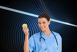Composite image of surgeon holding an apple and smiling at camera