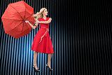 Composite image of woman posing with a broken umbrella