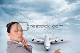 Composite image of thoughtful businesswoman pointing