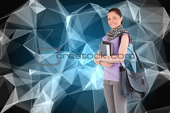 Composite image of student holding books and her bag while standing