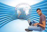 Composite image of man sitting using laptop and looking at camera