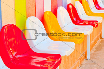 a number of multi-colored seats for children
