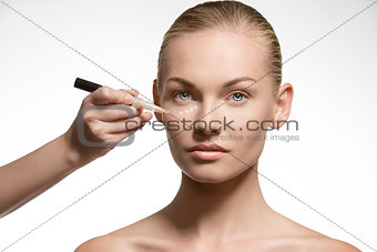 natural woman applying cosmetics on her visage