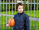 young basketball player holding ball against iron fence at the p