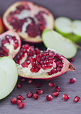 Pomegranate, pomegranate seeds and apple on a wooden board