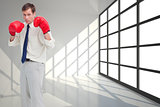 Composite image of businessman with his boxing gloves ready to f