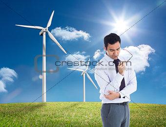Composite image of thinking businessman holding glasses
