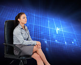 Composite image of portrait of a serious businesswoman sitting o