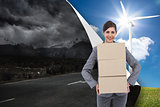 Composite image of smiling businesswoman carrying cardboard boxe