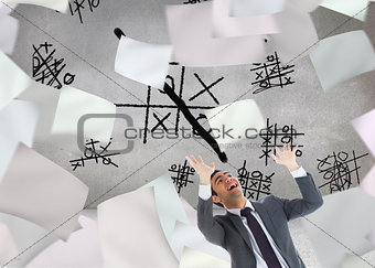 Composite image of scared businessman with arms raised