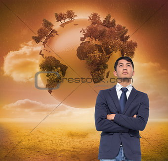 Composite image of unsmiling casual businessman with arms crosse