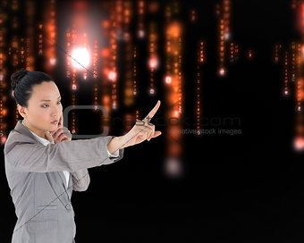Composite image of unsmiling thinking asian businesswoman pointi