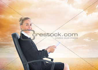 Composite image of businesswoman sitting in swivel chair holding