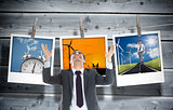 Composite image of happy  businessman with arms raised