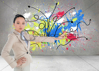 Composite image of unsmiling asian businesswoman pointing