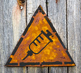 Syringe Icon on Rusty Warning Sign.