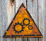Cogwheel Gear Icon on Rusty Warning Sign.