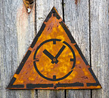 Icon of Clock Face on Rusty Warning Sign.