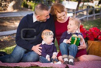 Small Young Family Opening Christmas Gifts in the Park