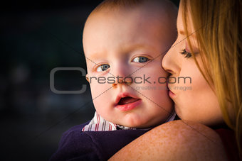 Adorable Red Head Infant Boy is Kissed By His Mother