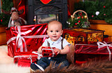 Cute baby boy with Christmas gifts