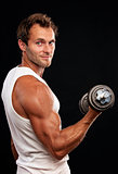Muscular man lifting dumbbell on black background