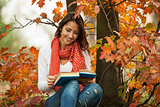 Young girl reading book in autumn park