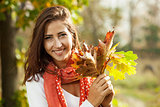 Young girl with autumn leaves in hand on sunny day
