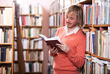 Handsome man reading book in library