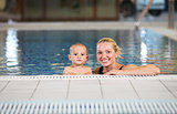 Young cheerful mother and little son in a swimming pool