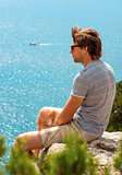Young Man relaxing Outdoor on rocky cliff sitting and looking on Sea Summer time Traveling Lifestyle