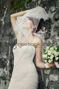 Beautiful bride playing with veil.