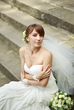 Happy young bride laying on steps.