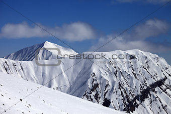 Off-piste slope with stones and mountains with trace of avalanch